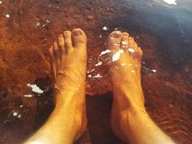 Feet in water. Feet in red very cold water Royalty Free Stock Photography