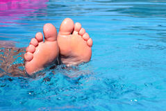 Feet in the water. Women feet in the water in the pool Stock Image