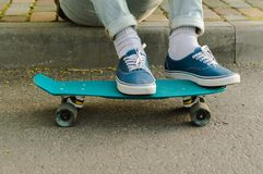 Penny skateboard commute hipster transport solutions. Feet weared in the blue canvas skate shoes standing at the blue plastic skateboard. Concept of the modern Stock Images
