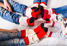 Feet wearing Christmas socks on wood floor. Happy family at home. Xmas holidays concept Royalty Free Stock Image