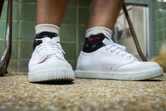 Feet wearing old fashion sport shoes Royalty Free Stock Photo