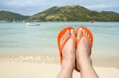 Feet Wearing Orange Flip Flop on a Beach 1 Stock Photo