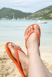 Feet Wearing Orange Flip Flop on a Beach 2 Royalty Free Stock Images
