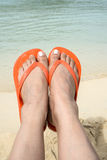 Feet Wearing Orange Flip Flop on a Beach 3 Stock Photos