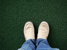 Feet wearing shoes standing on green carpet Royalty Free Stock Photography