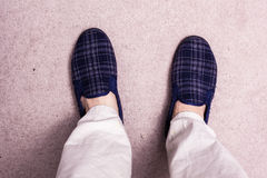 Feet wearing slippers on carpet stock photography