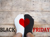 Feet wearing white and black socks with red heart shape. Black Friday concept. Selfie feet wearing white and black socks with red heart shape on wooden floor Stock Photos