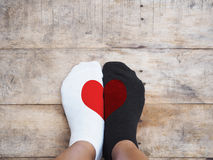 Feet wearing white and black socks with red heart shape. Selfie feet wearing white and black socks with red heart shape on wooden floor background. Love concept Royalty Free Stock Photos