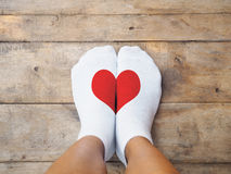 Feet wearing white socks with red heart shape. Selfie feet wearing white socks with red heart shape on wooden floor background. Love concept Royalty Free Stock Photo