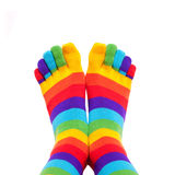 Feet wearing winter colorful striped socks. Isolated on white background Royalty Free Stock Photos