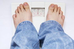 Feet on weight scale. Feet and weight scale isolated on white background Royalty Free Stock Photos