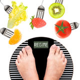 Feet on a weight scale. Fruits and vegetables Stock Photos