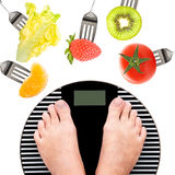 Feet on a weight scale. Fruits and vegetables Stock Images