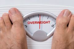 Feet on weight scale indicating overweight. Closeup of man's feet on weight scale indicating Overweight Royalty Free Stock Image