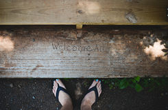 Feet with Welcome All sign. Image of feet in flip flops and the words `Welcome All` in concrete Royalty Free Stock Photo