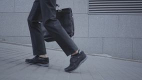 Feet of well-dressed boy walking on the street leading the ball and holding purse. Serious young man simultaneously stock footage
