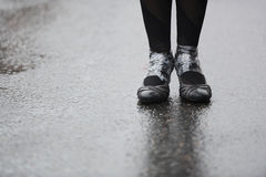 Feet on wet asphalt. Feet of the girl on wet asphalt Royalty Free Stock Image