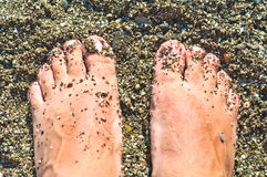 Feet on the wet shingle beach Stock Photos