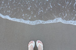 Feet in white Flip flops on the beach with sea water wave. Woman feet in white Flip flops on the beach with sea water wave and blank copy space for texting which Stock Photography