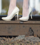 Feet in white shoe on the railway track Stock Images