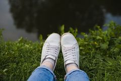 Feet in white sneakers on the grass by the river stock photography