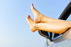 Feet  from the window of a car. Feet of a young girl from the window of a car Royalty Free Stock Photo