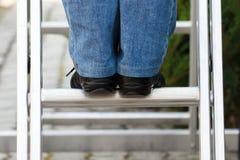 Feet of woman on aluminum ladder in garden Royalty Free Stock Photo