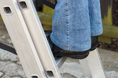 Feet of woman on aluminum ladder in garden Royalty Free Stock Image