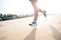 Feet of the woman that is jogging by the sea Stock Images