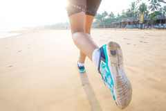 Feet of the woman that is jogging by the sea Stock Photos