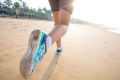 Feet of the woman that is jogging by the sea at the sunrise Royalty Free Stock Image