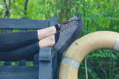 Feet of woman relaxing on bench Stock Photography