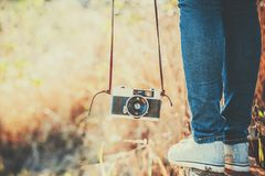 Feet of woman with retro camera. outdoor travel lifestyle Royalty Free Stock Photo