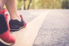 Feet woman running on the road for health. Color of vintage tone selective and soft focus Royalty Free Stock Photography