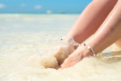 Feet of a woman in the spray of clean sea water. royalty free stock image