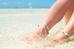 feet of a woman in the spray of clean sea water. royalty free stock images