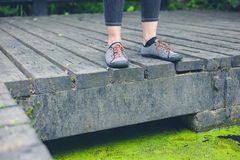 Feet of woman standing on deck by pond Royalty Free Stock Photos