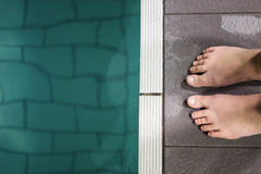 Feet of woman standing on the edge of the pool Royalty Free Stock Image