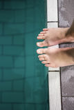 Feet of woman standing on the edge of the pool Royalty Free Stock Photos