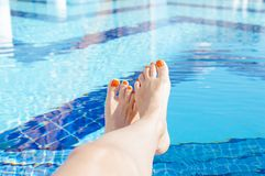 Feet of a woman on the swimming pool Stock Photo