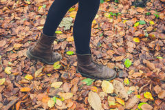 Feet of woman walking in leaves. The feet of a young woman wearing boots walking in some leaves in the autumn Royalty Free Stock Image