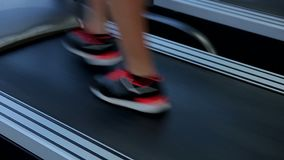 Feet of woman walking on treadmill to warm up before active workout in gym. Stock footage stock video footage