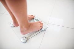 Feet of woman on weighting scale. At home royalty free stock photos