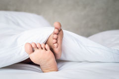 Feet of women on white bedding in the morning time Royalty Free Stock Photos