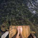 Feet on wooden pier Royalty Free Stock Photo