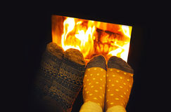Feet in wool socks of couple lovers warming by cozy fire. royalty free stock photos