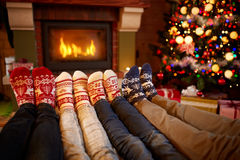 Feet in wool socks near fireplace in Christmas time Stock Images