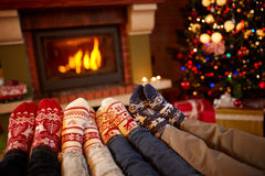 Feet in wool socks near fireplace in winter. Family at home near fire stock image