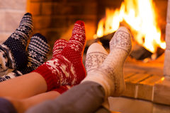Feet in wool socks near fireplace in winter Royalty Free Stock Images