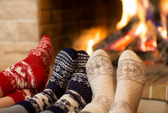 Feet in wool socks near fireplace in winter time Stock Photography